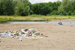 Pile of garbage in sand on bank the rive Royalty Free Stock Photos