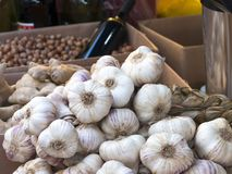 Pile of garlic heads of Vessalico exposed at a banquet of the ma. Rket. On the background a bottle of wine and hazelnuts from Piedmont on display Stock Photos
