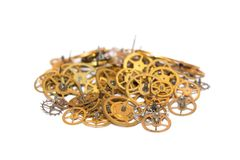 A pile of gear. Many mechanisms. Old vintage gears. Part of clockwork. The natural color and texture. Focus on front, blurred background. Golden cogs Royalty Free Stock Photo