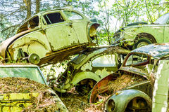 Pile of German Cars. Group of old wrecked and rusty cars in the forest Royalty Free Stock Image