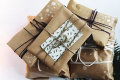 A pile of gift boxes in craft eco paper, handmade presents on wh stock photography