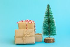 Pile of gift boxes wrapped in craft paper tied with twine red white ribbon Christmas tree on mint blue background. New Year royalty free stock image