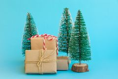 Pile of gift boxes wrapped in craft paper tied with twine red white ribbon Christmas trees on mint blue background. New Year. Corporate presents shopping royalty free stock photo