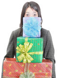 Pile of gifts. Young businesswoman standing and hiding behind a pile of colorful wrapped gifts she is carrying. Isolated over white. Caveat at full size: green Royalty Free Stock Photography