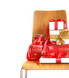 Pile of gifts on wooden chair against white Stock Image