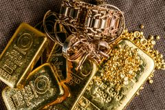 A pile of gold bars gold jewelry and gold granules on the background to the coarse texture of the textile stock image