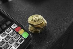 A pile of gold Bitcoin coins and POS terminal. Bitcoins Cryptocurrency. E-commerce, business, finance concept, banking. And paymant stock image