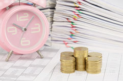 Pile of gold coin have blur old pink alarm clock Royalty Free Stock Images