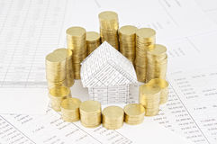 Pile of gold coins around house on finance account Stock Photo