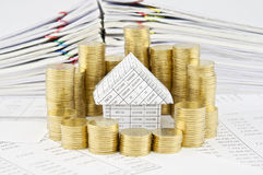 Pile of gold coins around house and pile of paperwork Royalty Free Stock Photography