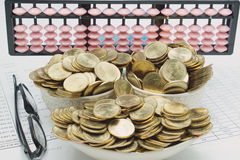 Pile of gold coins in ceramic as ship and spectacles Stock Photos