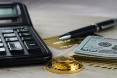 A pile of gold coins, dollar bills, gold credit card, pen and a calculator Stock Photo