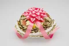 Pile gold coins in foam mesh wrapped with red ribbon Stock Photo