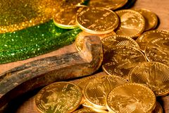 Pile of gold coins from green hat St Patricks Day. Treasure of pure gold coins from a green hat on rustic wooden table into horseshoe to celebrate luck on St Stock Image