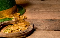 Pile of gold coins from green hat St Patricks Day. Treasure of pure gold coins from a green hat on rustic wooden table into horseshoe to celebrate luck on St Stock Photo