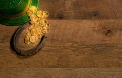 Pile of gold coins from green hat St Patricks Day. Treasure of pure gold coins from a green hat on rustic wooden table into horseshoe to celebrate luck on St Royalty Free Stock Photo