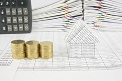 Pile of gold coins and house with calculator place vertical Stock Photo