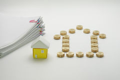 Pile of gold coins and house with pile overload document. With colorful paperclip on white background Stock Photo