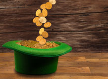 Pile of gold coins inside green hat St Patricks Day. Treasure of pure gold coins pouring down onto a green velvet hat on wooden table. Concept image to celebrate Stock Images