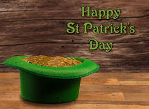 Pile of gold coins inside green hat St Patricks Day. Treasure of pure gold coins inside a green velvet hat on wooden table to celebrate luck on March 17th. Text Stock Photos
