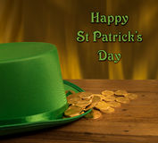 Pile of gold coins inside green hat St Patricks Day. Treasure of pure gold coins inside a green velvet hat on wooden table to celebrate luck on March 17th. Text Royalty Free Stock Images