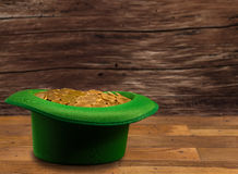 Pile of gold coins inside green hat St Patricks Day. Treasure of pure gold coins inside a green velvet hat on wooden table to celebrate luck on St Patrick`s Day Royalty Free Stock Images