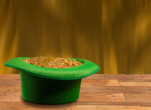Pile of gold coins inside green hat St Patricks Day. Treasure of pure gold coins inside a green velvet hat on wooden table to celebrate luck on St Patrick`s Day Stock Image