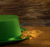 Pile of gold coins inside green hat St Patricks Day. Treasure of pure gold coins inside a green velvet hat on wooden table to celebrate luck on St Patrick`s Day Stock Images