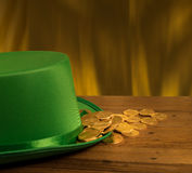 Pile of gold coins inside green hat St Patricks Day. Treasure of pure gold coins inside a green velvet hat on wooden table to celebrate luck on St Patrick`s Day Royalty Free Stock Image