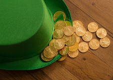 Pile of gold coins inside green hat St Patricks Day. Treasure of pure gold coins inside a green velvet hat on wooden table to celebrate luck on St Patrick`s Day Royalty Free Stock Photos