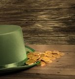 Pile of gold coins inside rim of green hat St Patricks Day. Treasure of pure gold coins inside the rim of a green velvet hat. Placed on wooden table to celebrate Stock Photography