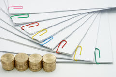 Pile of gold coins and pile of document. With colorful paperclip on white background Royalty Free Stock Photos