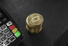 A pile of gold Dash Crypto currency coins and POS terminal. Dashes Cryptocurrency. E-commerce, business, finance concept. Banking and payment stock photo