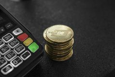 A pile of gold Dash Crypto currency coins and POS terminal. Dashes Cryptocurrency. E-commerce, business, finance concept. Banking and payment royalty free stock image