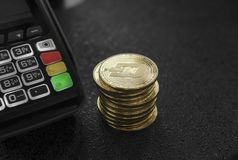 A pile of gold Dash Crypto currency coins and POS terminal. Dashes Cryptocurrency. E-commerce, business, finance concept. Banking and payment stock image