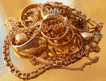 Pile of gold jewelry. On a gold background royalty free stock photos