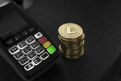 A pile of gold Litecoin Crypto currency coins and POS terminal. Litecoins Cryptocurrency. E-commerce, business, finance. Concept, banking and payment stock photo
