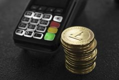 A pile of gold Litecoin Crypto currency coins and POS terminal. Litecoins Cryptocurrency. E-commerce, business, finance. Concept, banking and payment royalty free stock photo