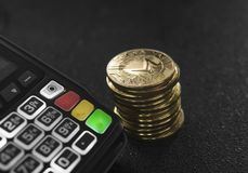 A pile of gold Monero Crypto currency coins and POS terminal. Moneros Cryptocurrency. E-commerce, business, finance. Concept, banking and payment stock image