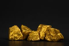 A pile of gold nuggets or gold ore on black background, precious stone or lump of golden stone, financial and business concept. Idea stock image
