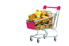 Pile of gold nuggets or gold ore in shopping cart or supermarket. Trolley on white background, precious stone or lump of golden stone, financial and business royalty free stock image