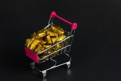A pile of gold nuggets or gold ore in shopping cart or supermarket trolley on black background, precious stone or lump of golden. Stone, financial and business royalty free stock images