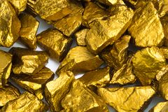 A pile of gold nuggets or gold ore on white background, precious stone or lump of golden stone, financial and business concept. Idea stock images
