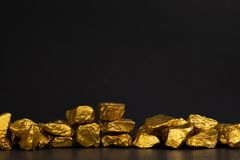 A pile of gold nuggets or gold ore on black background, precious stone or lump of golden stone, financial and business concept. Idea royalty free stock image