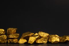 A pile of gold nuggets or gold ore on black background, precious stone or lump of golden stone, financial and business concept. Idea stock images