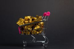 A pile of gold nuggets or gold ore in shopping cart or supermarket trolley on black background, precious stone or lump of golden. Stone, financial and business stock image