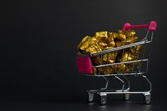A pile of gold nuggets or gold ore in shopping cart or supermarket trolley on black background, precious stone or lump of golden. Stone, financial and business royalty free stock photography