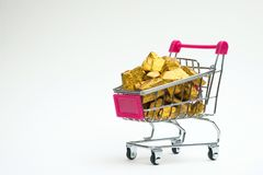 Pile of gold nuggets or gold ore in shopping cart or supermarket. Trolley on white background, precious stone or lump of golden stone, financial and business stock image