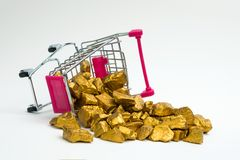 Pile of gold nuggets or gold ore in shopping cart or supermarket. Trolley on white background, precious stone or lump of golden stone, financial and business stock photography