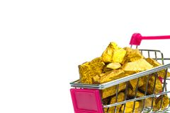 Pile of gold nuggets or gold ore in shopping cart or supermarket trolley on white background, precious stone or lump of golden. Stone, financial and business stock photography